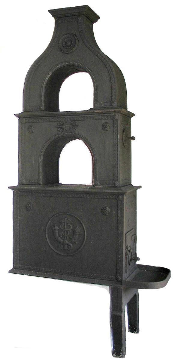 Midt på sideplaten: Korslagte overflødighetshorn med Merkurstav i sirkel. Løpende hund-bord  langs overkant og sider, rosett  i øvre hjørner og et ornament  øpm