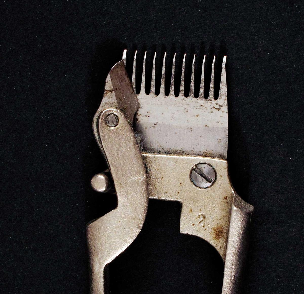 """Hårklipper, enkel håndtype, """"kam"""" , som på en elektrisk klippemaskin, med en bevegelig kniv, montert på et handtak, og festet i hver sin ende a en bøyle/fjær.   Av fem deler, som er skrudd sammen."""