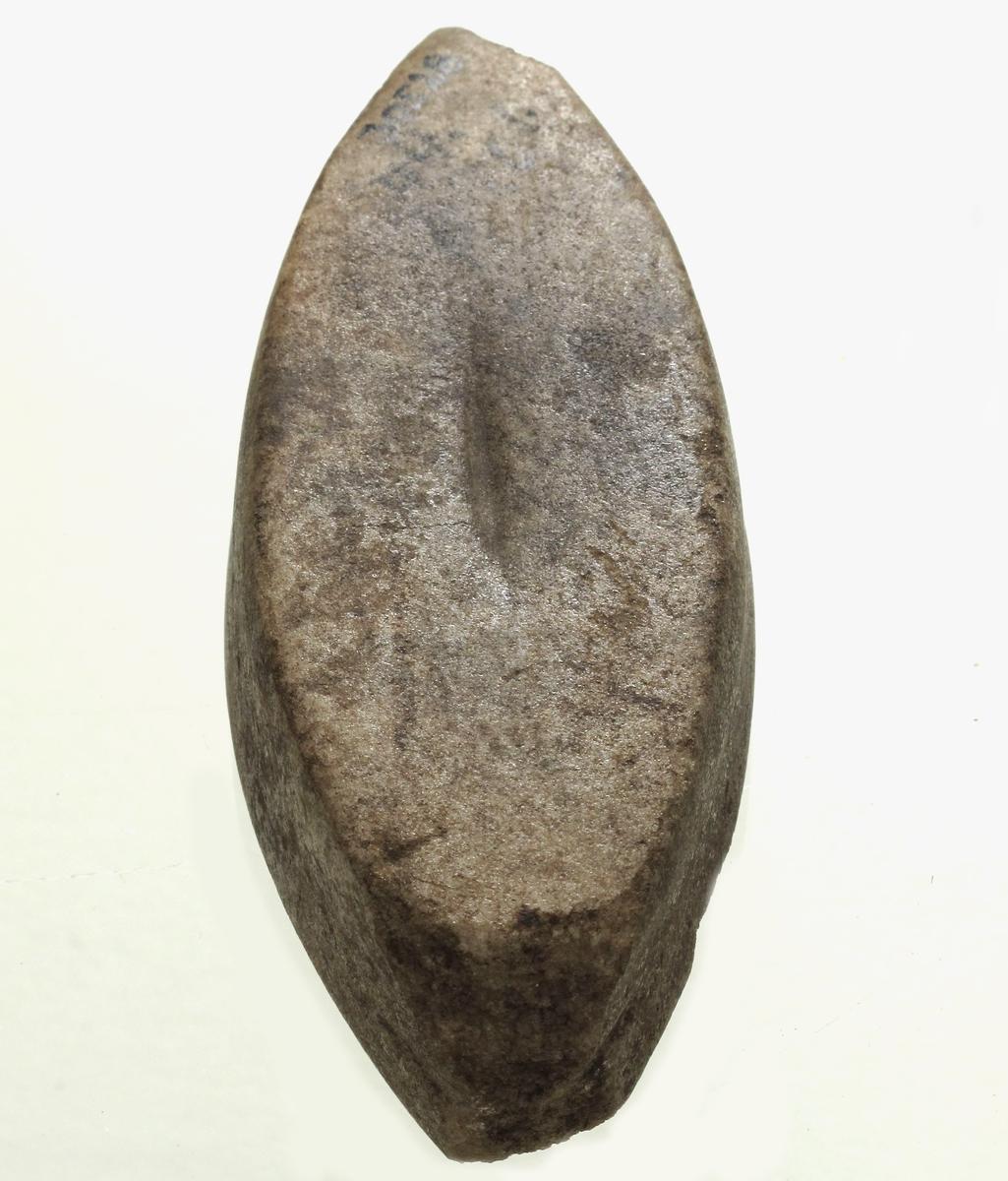 Beltestein av lys grålig kvartsitt, av typen [Rygh fig.155]R. 155, men korte. Bruksspor på oversiden. Endene noe avslått, ellers bra bevart. Nåv. lengde 11,2 cm, st. bredde 4,4 cm.