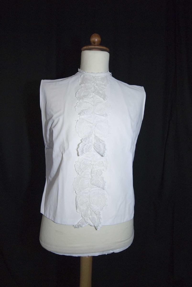 Hvit damebluse uten ermer lukket bak, blonder langs hele fronten og rundt halslinningen. Lagt opp ekstra nede.