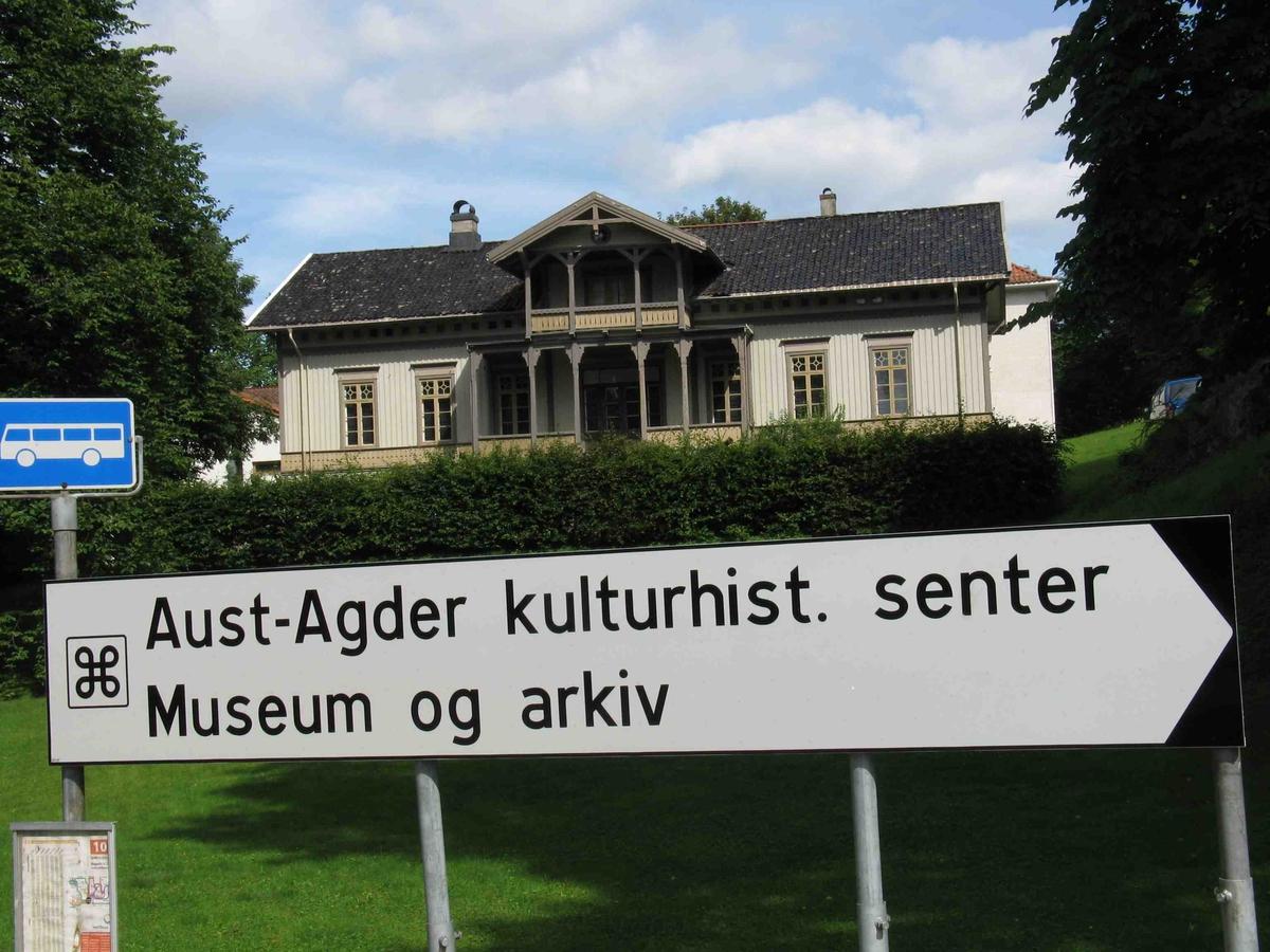 Skilt i veikrysset Parkveien - Hovet. Hvit henvisningsskilt med tekst og valknutesymbol, severdighet.  I bakgrunnen Langsæ gård. Busstoppskilt.