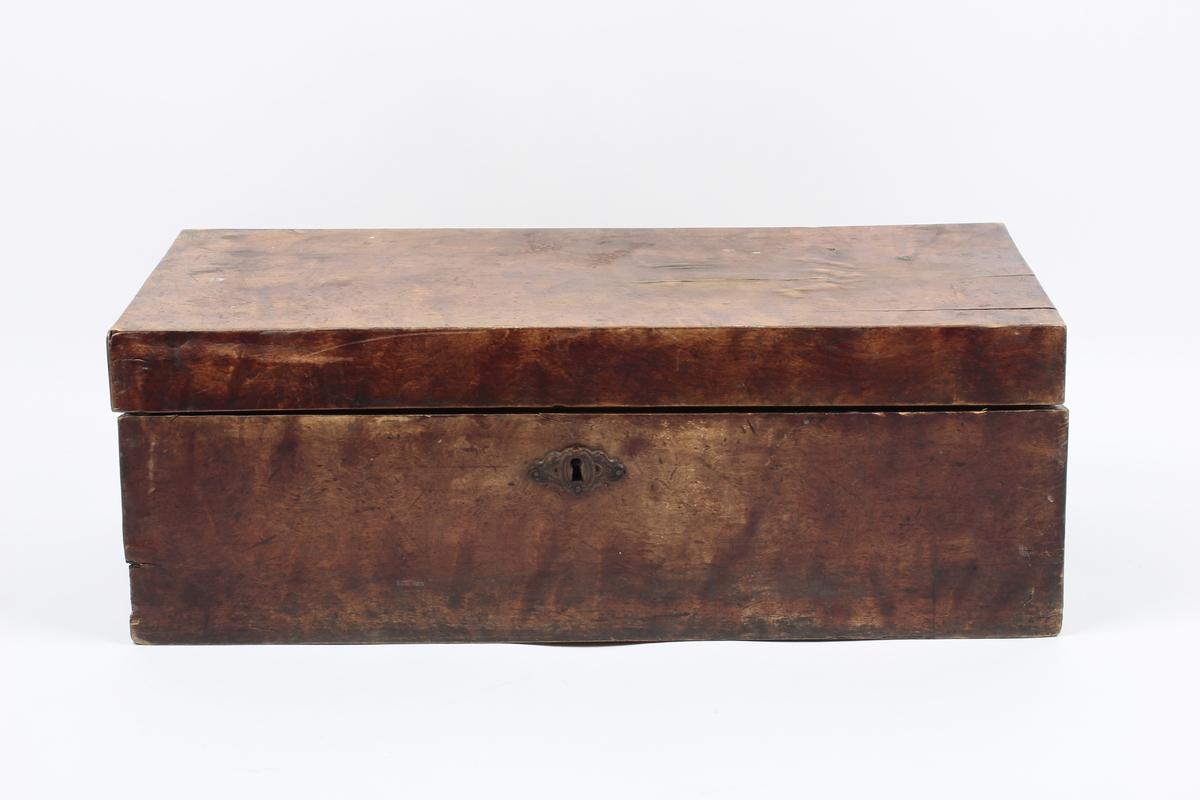 """Kontorkoffert av tre. Inneholder skriveplate og 6 bøker og 2 blekkbeholdere av glass. Den ene inneholder flytende blekk. Brukt av presten når han var ute i oppdrag. Form: Rektangulær.  A: Koffertkasse B: Skriveplate C: Blekkhus (nyere, med plastlokk): Pelikan D: Blekkhus (nyere, med plastlokk): Pelikan 4001 Königsblau E: Bok : """"Salmer og aandelige sange"""" F: Bok: """"Dr. Martin Luthers liden Katechismus"""" G: Bok: """"Nedre Borgesyssels Prosties Børne-Casses Fundatz"""" H: Bok: """"Almanak for Aaret efter Christi Fødsel 1888"""" I: Bok: """"Den anden Esra Bog"""" J: Håndskrevet hefte"""
