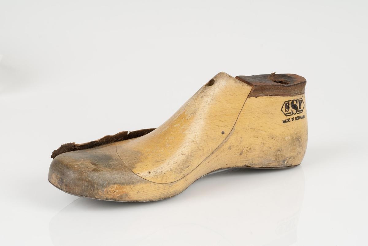 En tremodell i to deler; lest og opplest/overlest (kile). Høyrefot i skostørrelse 38, og 8 cm i vidde. Såle i metall.
