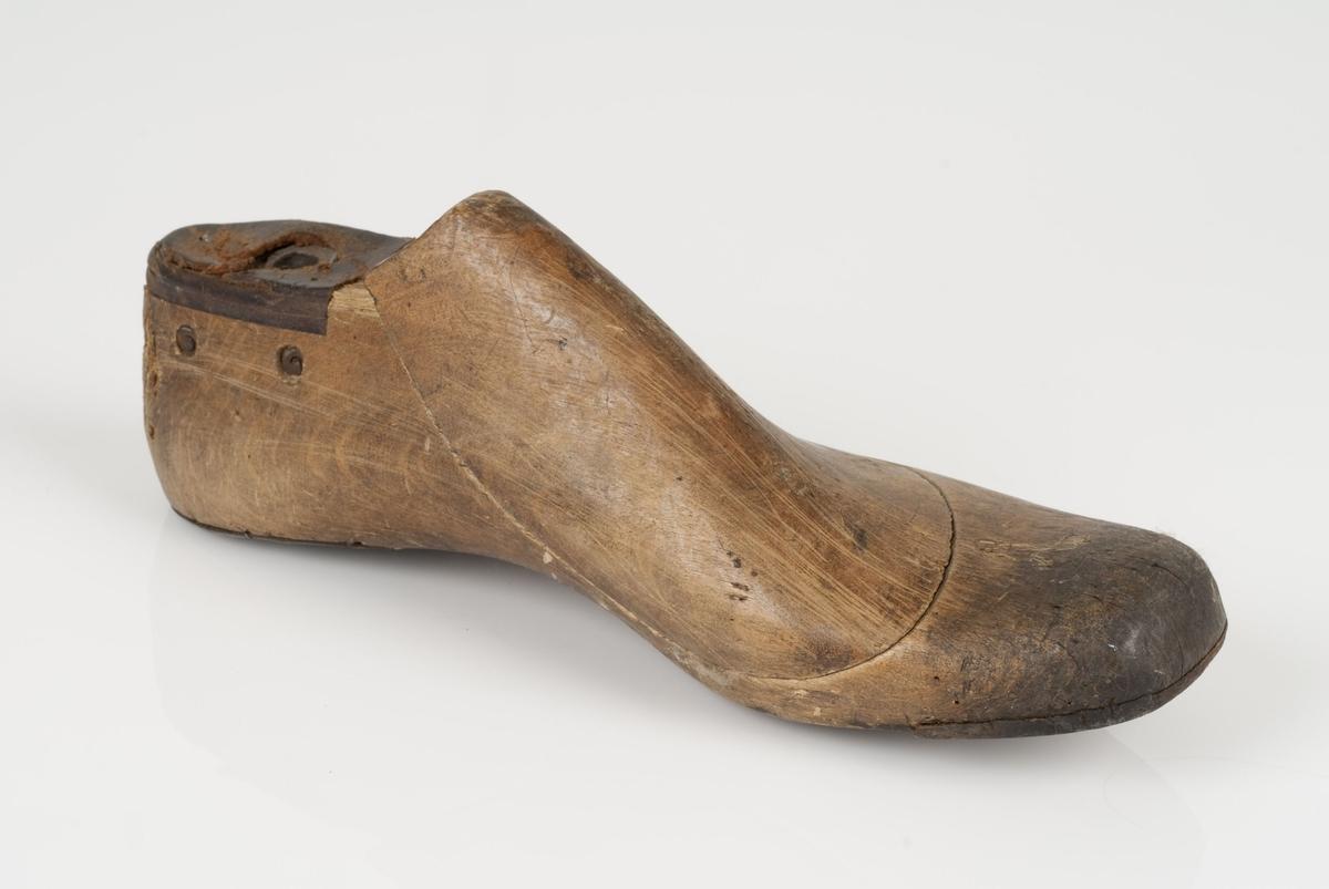 En tremodell i to deler; lest og opplest/overlest (kile). Venstrefot i skostørrelse 43, og 8 cm i vidde. Lestekam i skinn. Hælstykket i metall. Tåspringsåle i skinn.