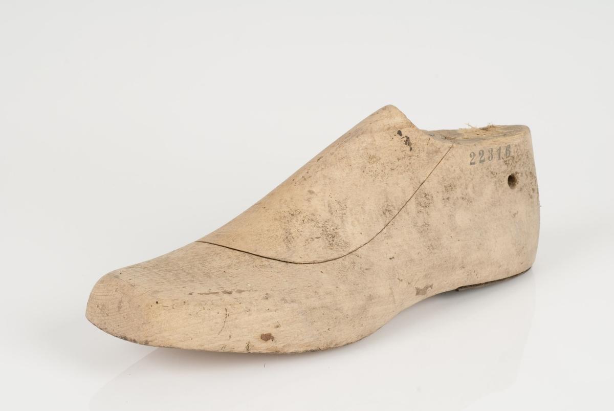En tremodell i to deler; lest og opplest/overlest (kile), med påført tekst. Venstrefot i skostørrelse 43 med 9 cm i vidde. Hælstykket er av metall.