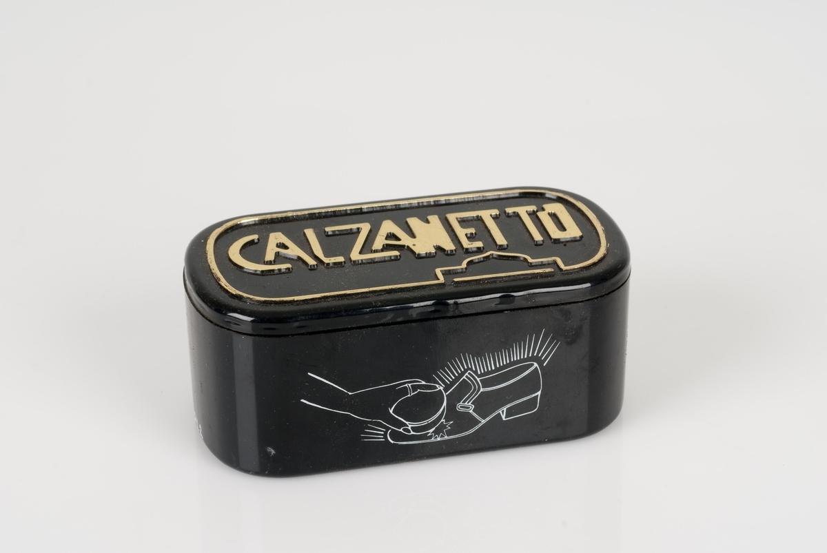Pussesvamp til sko i sort plastbeholder. Påført tekst og bilde på beholderen. En hvit merkelapp med priskode på undersiden av beholderen.