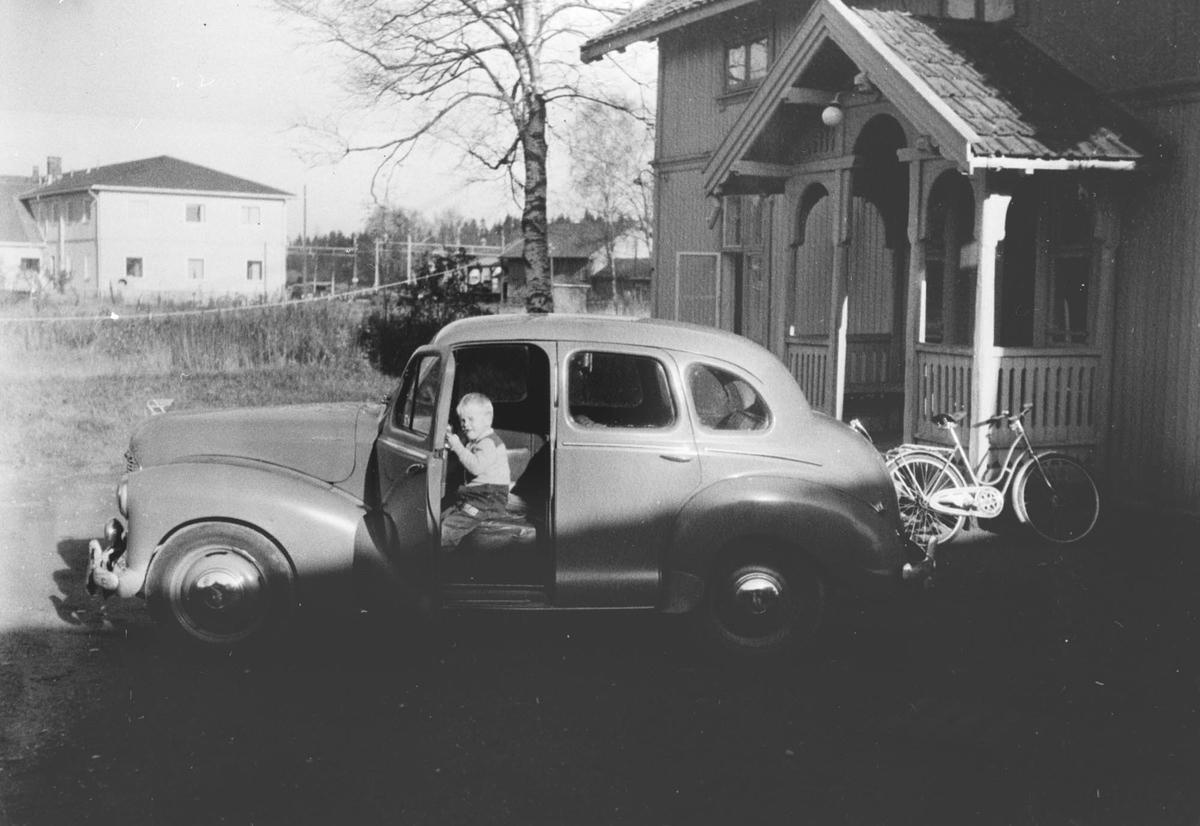 Liten gutt sitter i bil ved Nylund.