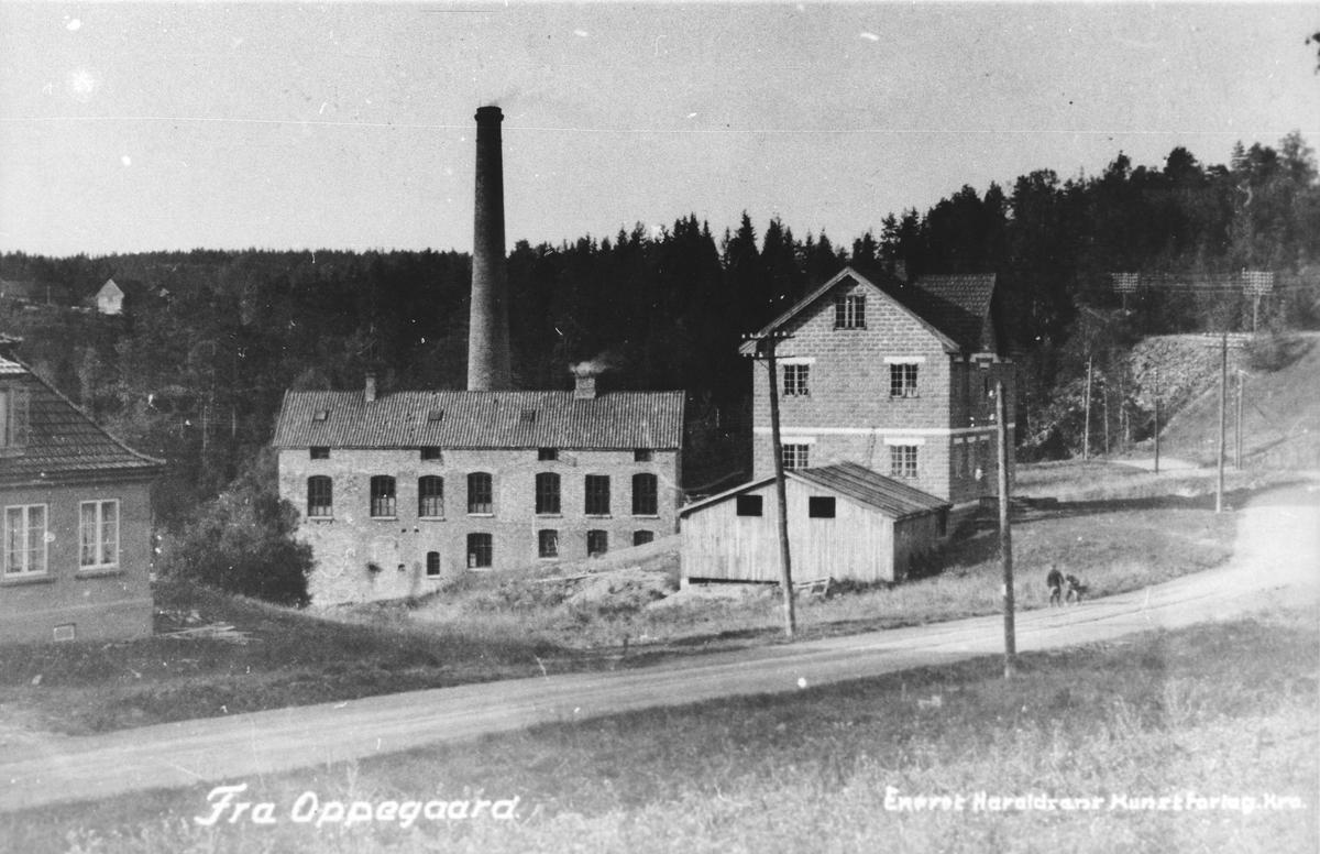 Fabrikkområde (trevare) med høy pipe og bygninger i tegelstein.