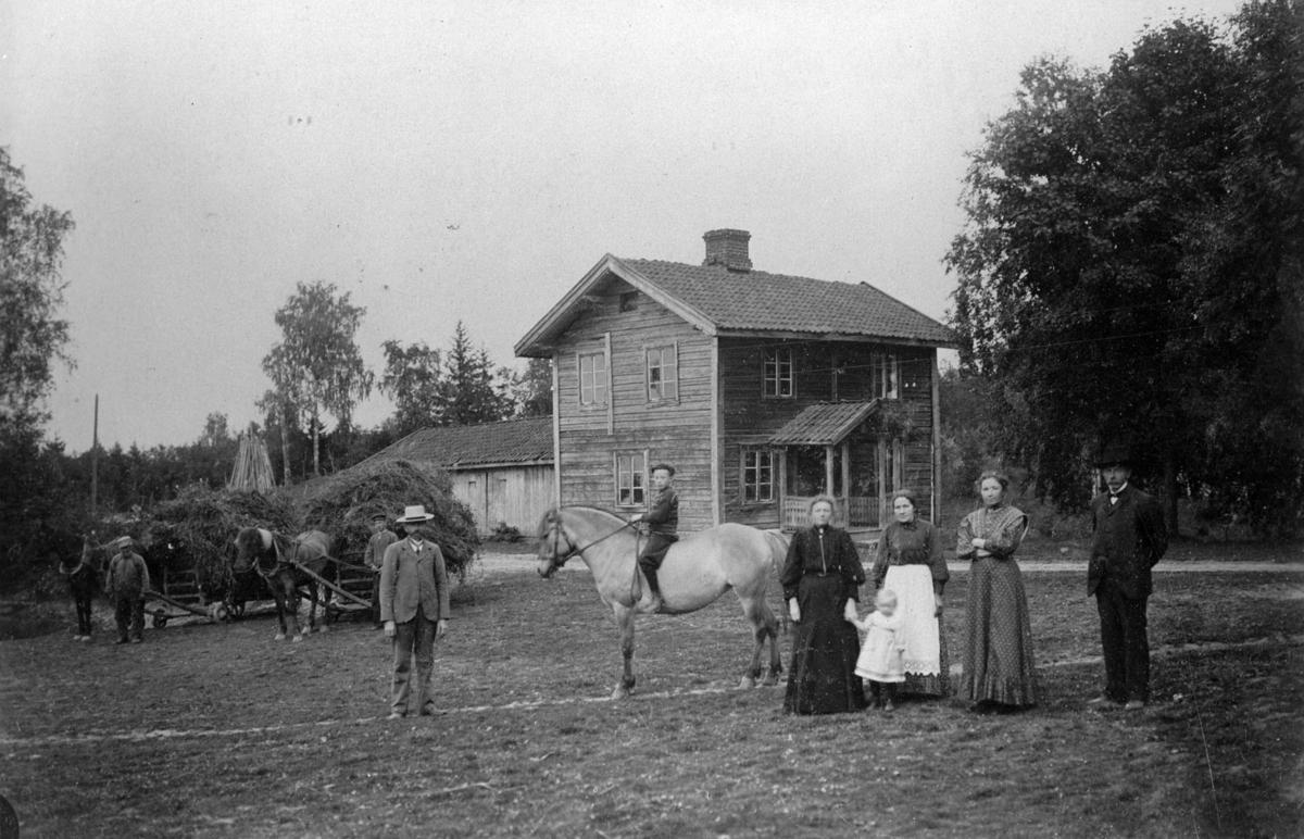 Karl Jacobsen Hilton med familie utenfor et lite 2-etasjes hus. En gutt rir på en fjording 2 hester med fulle høyvogner og hestekarer ser på.Uthus i bakgrunnen