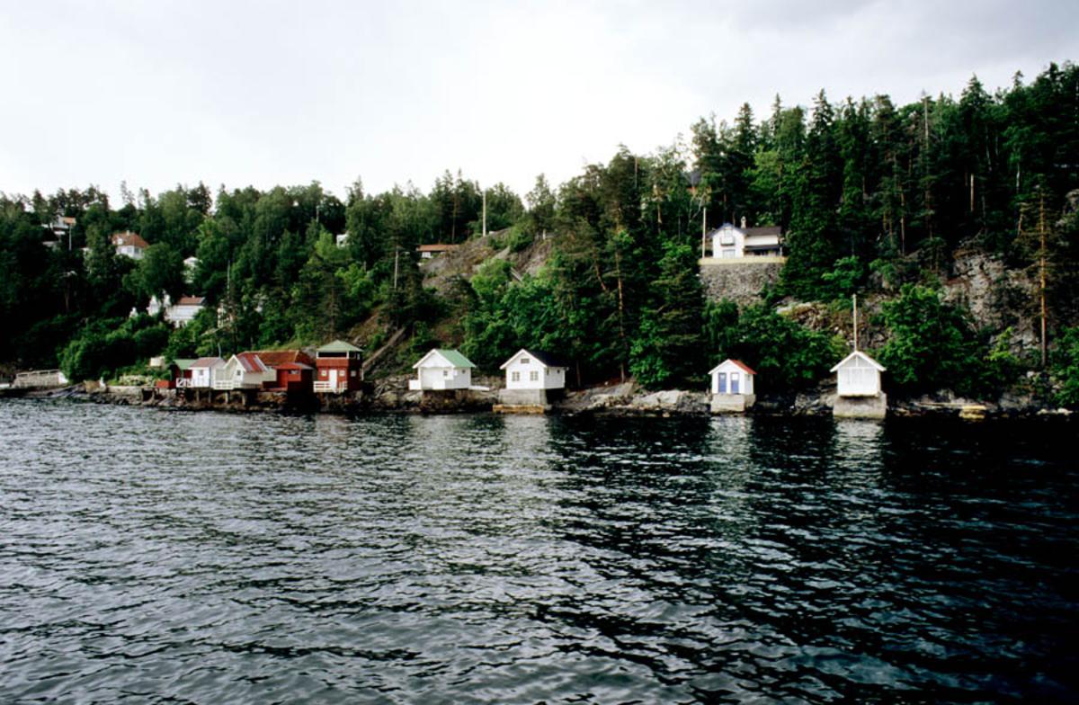 Oslofjorden. Kystlandskap med badehus liggende langs strandkanten. Trolig Nesoddlandet?