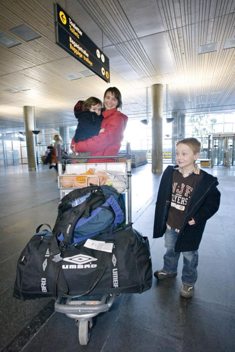 Vesker. Bagasjeutlevering innland. Mor med to barn og bagasje. Fotodokumentasjon i forbindelse med dokumentasjonsprosjekt - Veskeprosjektet 2006 - ved Akershusmuseet/Ullensaker Museum.