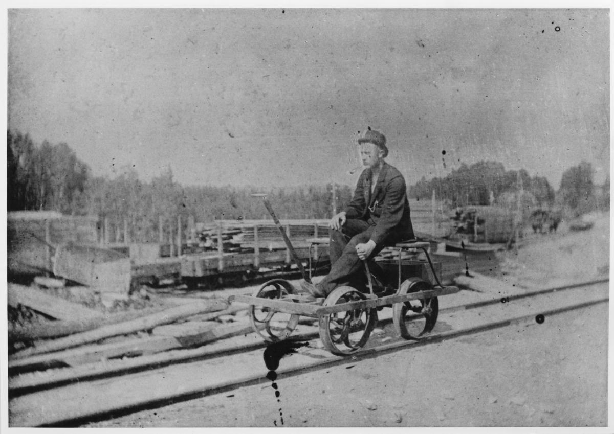 Pumpedressin med uidentifisert person. I bakgrunnen omlastingssporene på Bingsfos stasjon med To-vogner lastet med plank som skal lastes om til normalsporede vogner for transport til Oslo (Kristiania).