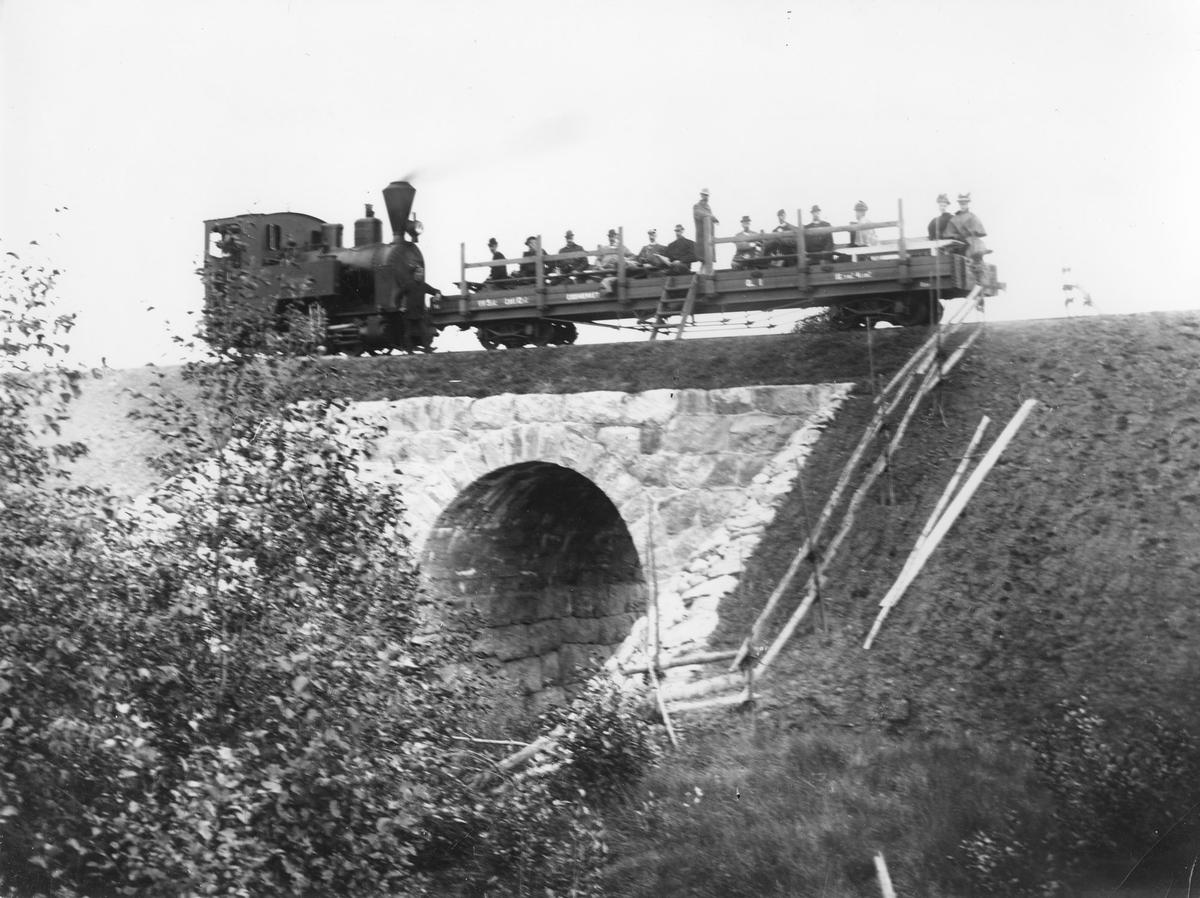 Inspeksjonstog ved Steinsrud kulvert sommeren 1896. En av Eidsverkets privatvogner er påmontert karmer og benker for passasjertransport. Anders Olai Haneborg m/frue er blant passasjerene.
