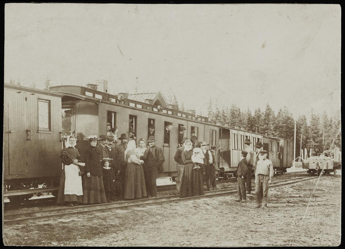 Reisende og pyntet lokalbefolkning ved togankomst på Hjellebøl stasjon, muligens i forbindelse med mobilisering av styrker til Urskog fort 18. september 1905.