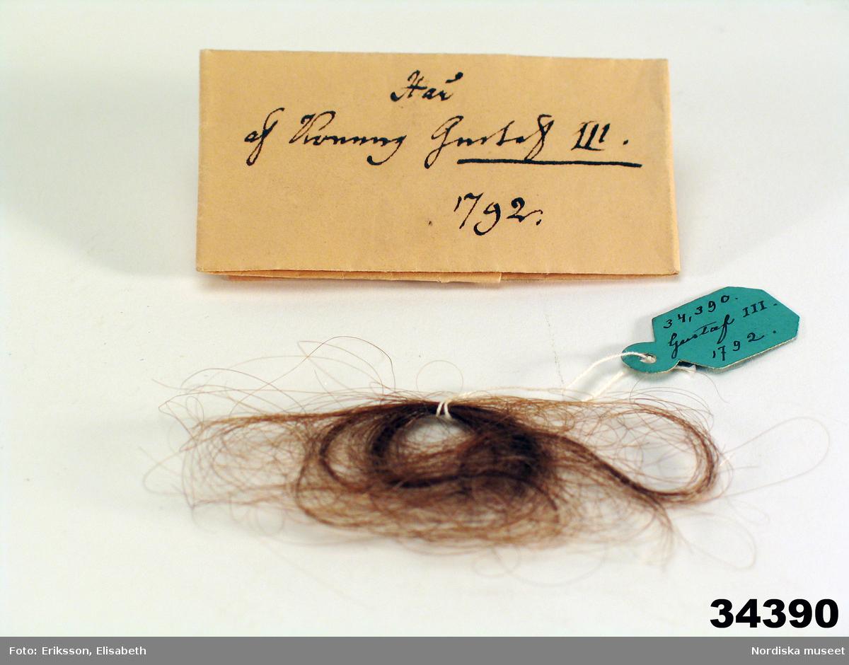 """Huvudliggaren: """"Konung Gustaf IIIs hår. 1792. G[åva] af sekret. L. Boberg i Stockholm 27/12 1882."""""""
