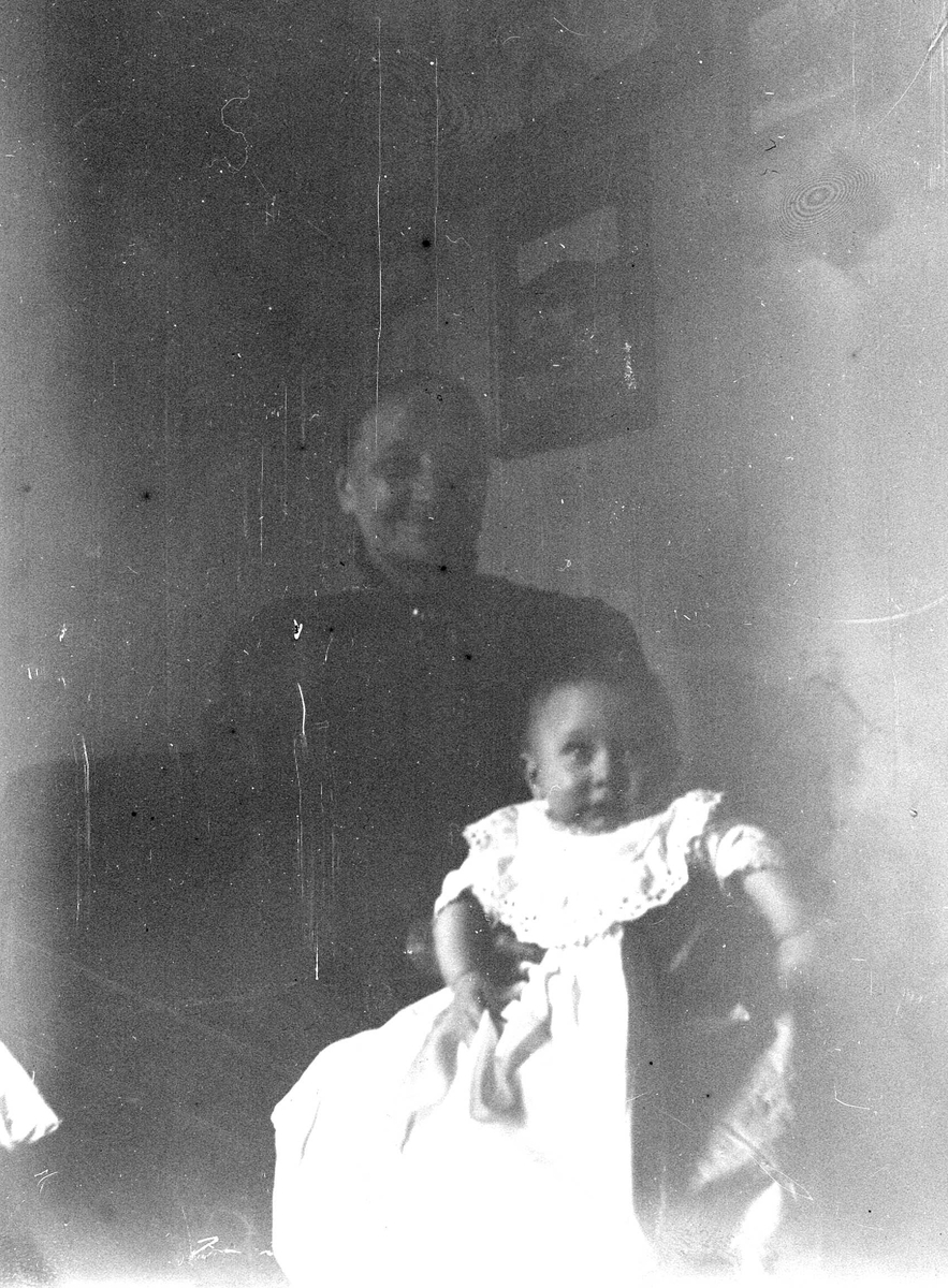 Dåpsbarn i dåpskjole på fanget til en eldre kvinne i interiør (mørk bakgrunn).Ukjente.Noe uskarpt bilde. Fra malerinne Juliane Fredrikke Langbergs (1856-1930) samling, tatt ca.1895-1910 med motivkrets slekt og venner samt steder tilknyttet samvær med disse.