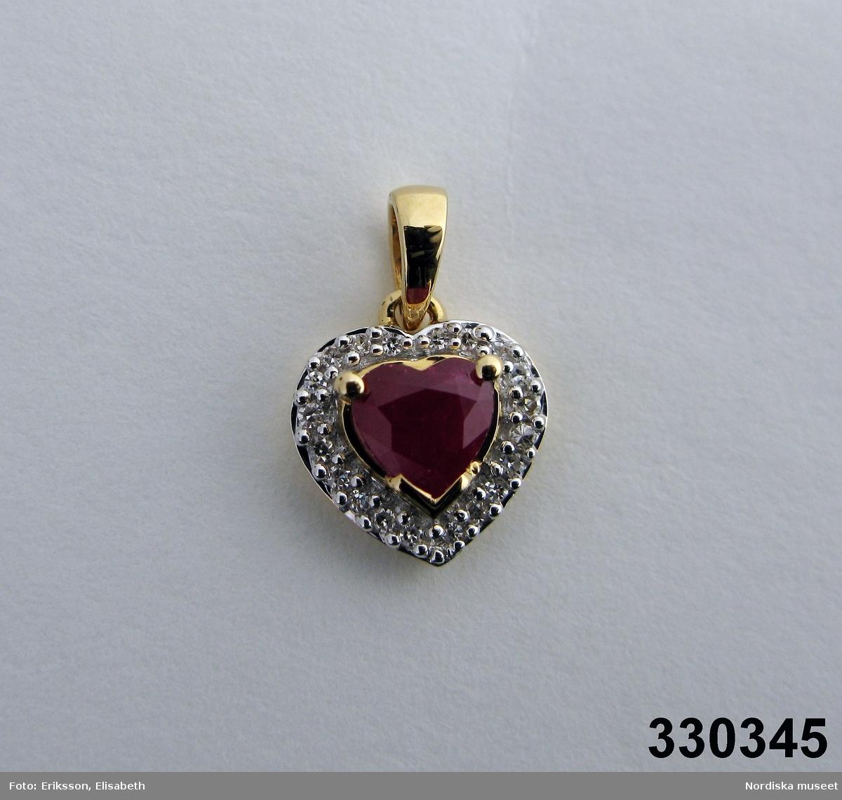 Hänge i form av ett hjärta. Tillverkad av rött guld med en hjärtformad facettslipad rubin i mitten omgjärdad av 36 st diamanter. Ädelstensvikten är för rubinen 0,61 ct och för diamanterna 0,108 ct. Ingrid Roos 2010-03-04