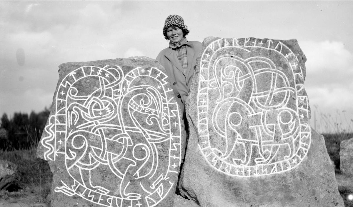 Kvinna vid parmonument med runstenar i Back-Norrby, Vårfrukyrka socken, Uppland