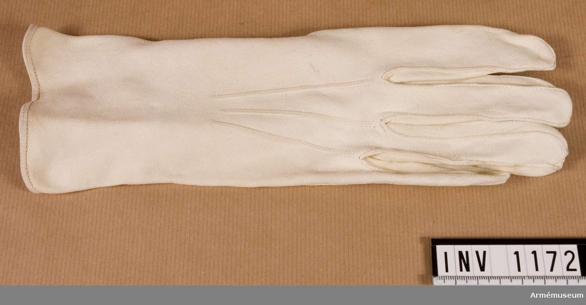 Handske H. Herrhandske av vitt sämskskinn. Laskade sömmar och sprund mitt under handleden. Knäppt med två vita knappar, s k tryckknappar.