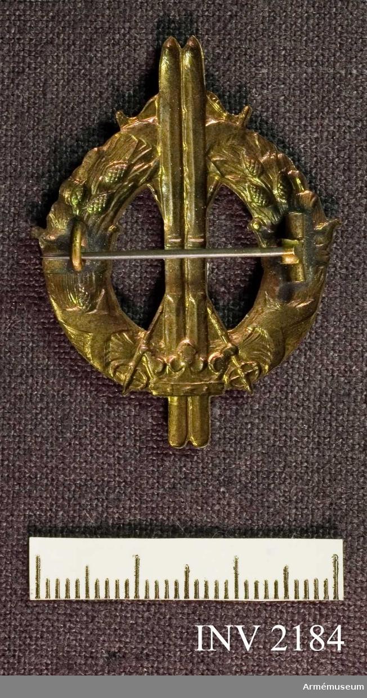 Samhörande nr är 2170-2188.Märke, skidlöpar-, brons, generalitetet.Lagerkrans med tre kronor och ett par upprättstående skidor. Nål på baksidan för fastsättning. Märket erövrat av general Almgren.
