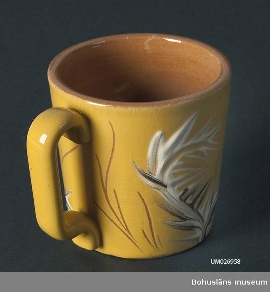 """106 3231 353 52 Keramikmugg med öra. Av lergods med gul glasyr utvändigt, genomskinlig glasyr invändigt. Dekorerad på utsidan med växtmotiv i vit och brun glasyr och inristade stjälkar? och text: """"Strömstad"""". I de inristade linjerna syns lerans ljust rödaktigt bruna färg. Närmast cylinderformad men något utställd eftersom mynningen är större än bottenplattan. Örat, med tillplattad form på mitten, sträcker sig längs hela muggens höjd. Stämplad undertill """"SYCO 779-GUL"""". Krackelerad yta. Föremålen UM26956 - UM26959 kommer från en loppisaffär i Vänersborg våren 1999. Kommentar till beslutet att anta föremålen till museets samlingar: """"Fritidsföremål"""" som passar bra in i vår nuvarande insamlingspolicy."""
