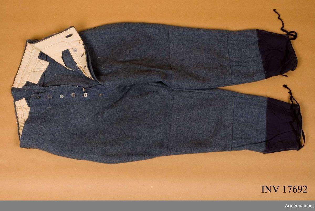 Grupp C:1. Ur uniform m/typ 1923 (blå) för manskap för 24.  infanteriregementet förlagt i Paris, Frankrike, bestående av: vapenrock, byxor, kappa, benlindor, halsduk, hjälm, livrem med tre patronväskor, hängslen, bajonetthylsa, bärremmar, ränsel av kanfas, kokkärl, tältduksdelar, tältstångsdelar, tältpinne, filt, dricksflaska med yllefoder, mattornister, kängor, skjorta, dödsbricka, gevär med bajonett plus figur. Byxor av gråblått (horisontblått) kläde som har två fickor på sidorna. Byxorna har sprund med knappar. Vid knäna förstärkningar, som är fastsydda vid byxbenen. Litteratur: Handbuch der Uniformenkunde. Prof. R. Knötel, Hamburg 1937. Vid franska armén infördes år 1915 i stället för  den gamla fredsuniformen en ny av horisontblått kläde.