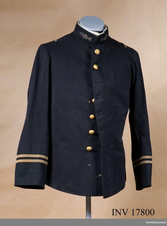 """Grupp C. Ur uniform för löjtnant vid Främlingslegionen, Frankrike. 1893. Buren av Ivan Törnnes Edward Aminoff. Uniformen består av vapenrock, långbyxor, mössa, officerssabel. Vapenrock av mörkblått kläde, enradig med sju knappar, 60 cm lång, åtsittande. På baksidan tvåuddigt lock; på varje udd två knappar. Till höger vid rockens nedre kant finns ett hål för sabel. Epålettsleif av guldlagon, 1 cm bred. Foder av svart  sidentyg med en innerficka på vardera sida. Knappar, förgyllda, 2,3 cm i diameter; sju på bröstet, fyra på baksidan. Med en diameter om 1,5 cm: tre på varje ärmuppslag. På knapparna finns ingraverat """"Légion étranger"""". Krage, upprättstående, av samma  svarta kläde med raka vinklar, 4,5 cm hög. På kragen finns klaffar av svart tyg med broderade främlingslegionstecken - flammande granat. Kragen är försedd med två hyskor och hakar samt fodrad med svart kläde. På kragens insida finns fyra  knappar för att knäppa på en vit krage. Kragen har firmastämpel """"Militär ekipering A/B Stockholm"""" och """"Linneuniform extra 41"""". Ärmuppslagen har tre knappar, 1,5 cm i diameter, och två guldgaloner, 1,5 cm breda på varje (två galoner är löjtnants gradbetäckning.)  Litteratur: Arméenalbum II Frankreich. Die Französichen Armée Leipzig, Verlag von M. Ruhl. sid 26: Fremdenregimenter.  Officerarna har samma uniform och gradbetäckningar som i  infanteriet, men knapparna har ingraverat påskriften: """"Légion étrangere"""". Bilaga sida 15. """"Abzeichen der militärische Grade"""" - Löjtnant har två galoner på ärmuppslaget. Sida 18. Första och andra raden knappar. - Främlingslegionen har knapp av gul metall med påskriften """"Légion étrangere"""". Den introducerade Svenska adelns ättartavlor. Gustav Elgenstierna Stockholm, sid 77 Aminoff Tab. 23 Ivan, Tönnes,  Edward. Kort biografi. Handbuch der Uniformenkunde, Prof R. Knötel, Hamburg 1937 sid 160, 1871-1915. År 1893 infördes i franska armén enradig vapenrock för officerarna. Enligt kapten W Granberg."""