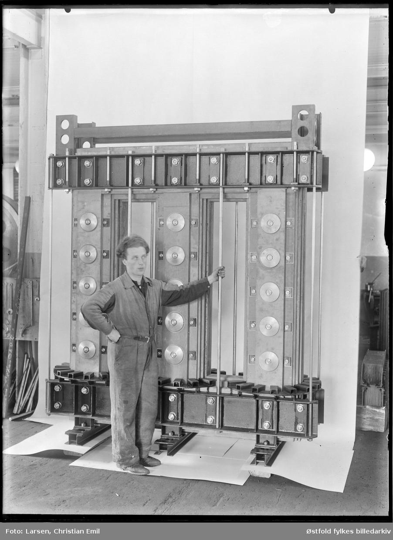 Produktfoto av transformator, 1945, ukjent fabrikk og ukjent sted i Sarpsborgdistriktet. Ukjent mann i kjeledress.