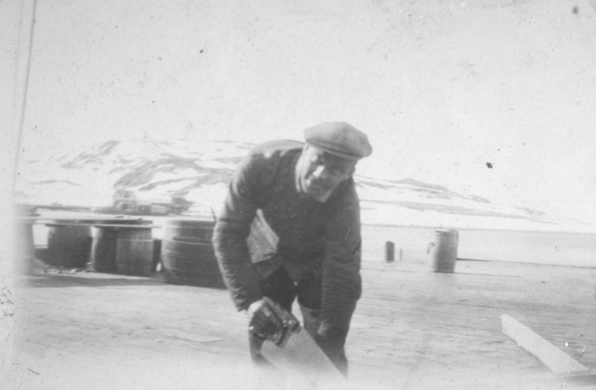 En mann sitter på huk og sager. Sted og person er ukjent, men bildet kan være tatt i Kvalsund kommune.