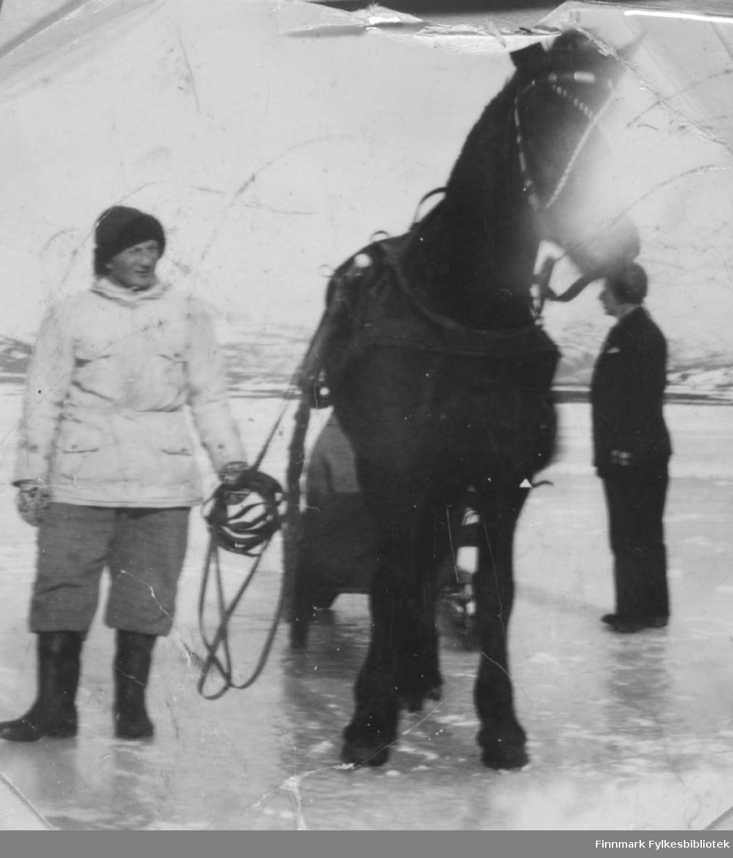 Johannes Nymo ute på havisen ved Brennelv i Porsanger med hesten Virda. En delvis skjult person sitter i sleden og en ukjent mann står til høyre på bildet.