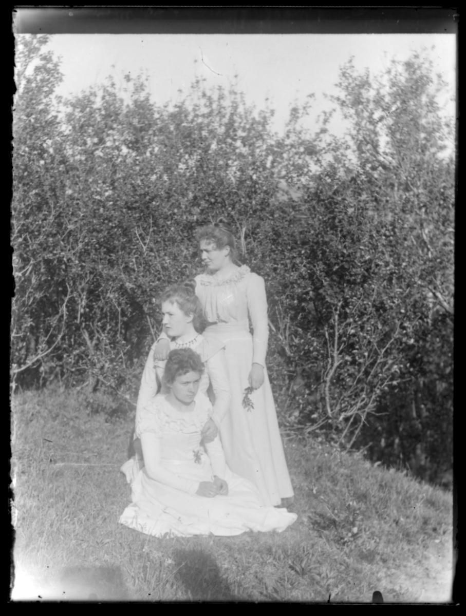 Tre kvinner i hvite sommerkjoler fotografert ute