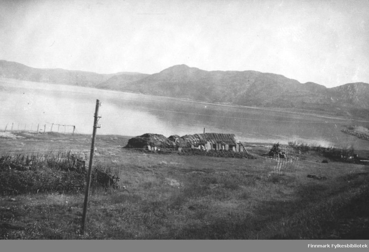 En torvgamme fotografert mot fjord på sommerhalvåret.