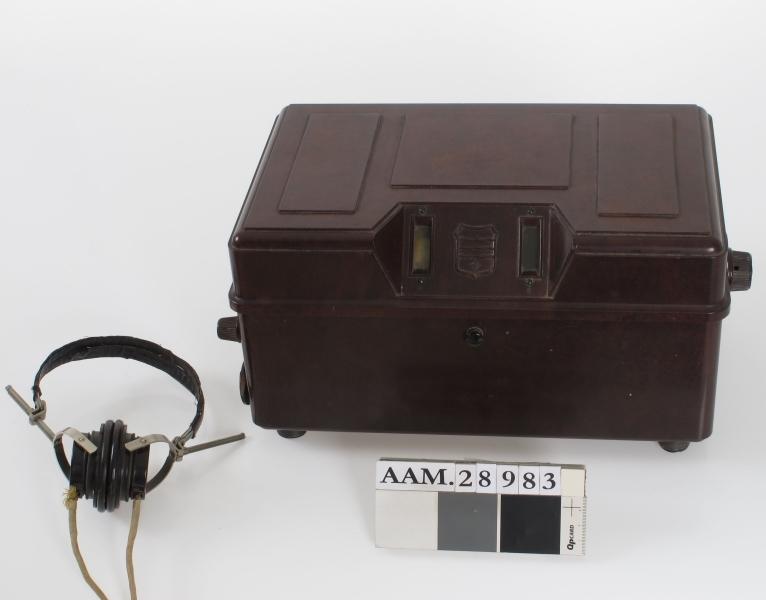 Kompakt radioapparat, boks av bakelitt. Tilhørende øreklokke med lednig.