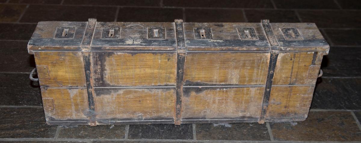 Lang smal kasse med lokk og jernbeslag. Den har tre fester til hengelås og håndtak på sidene.