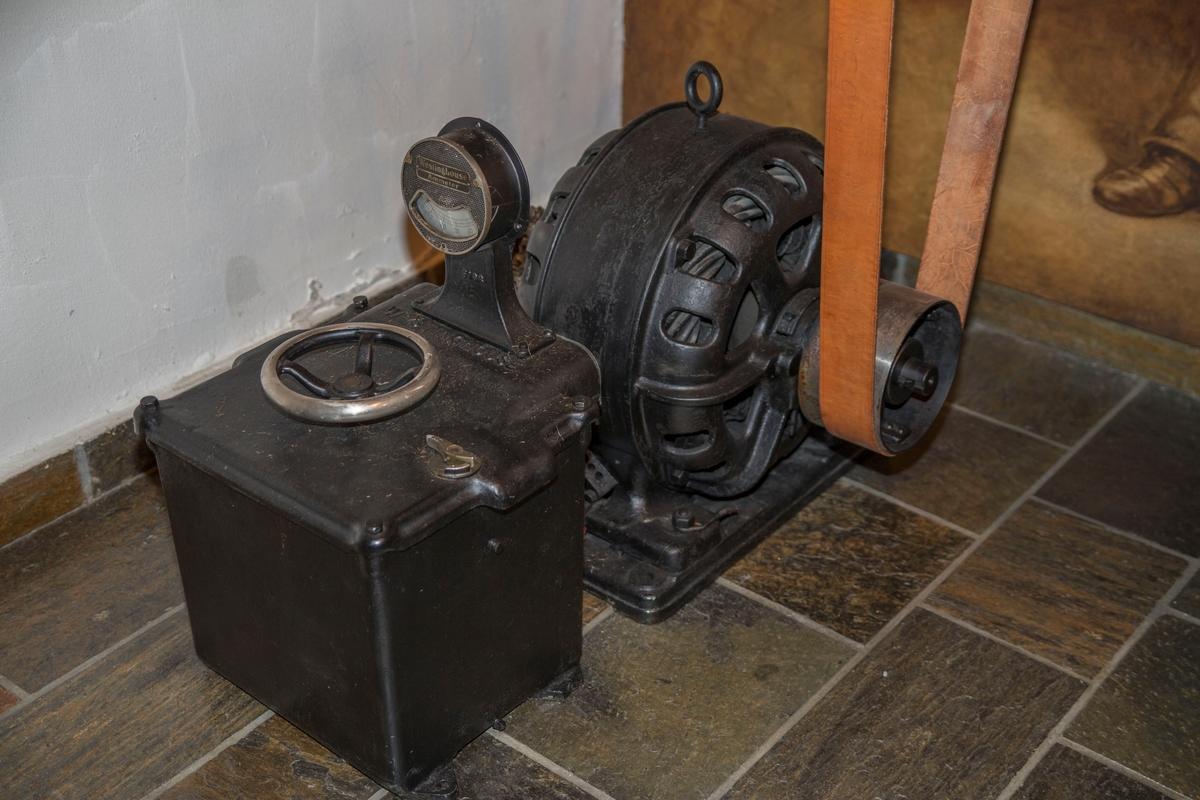 Sylinderformet induksjonsmotor koblet til en rektangulær boks som har innebygget startmotstand. Kassen har ett ampermeter på toppen.