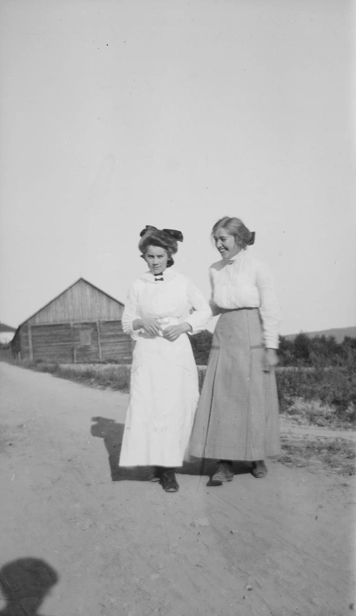 Celina Marie Mathiesen og en annen ung kvinne står på en grusvei i landlige omgivelser.