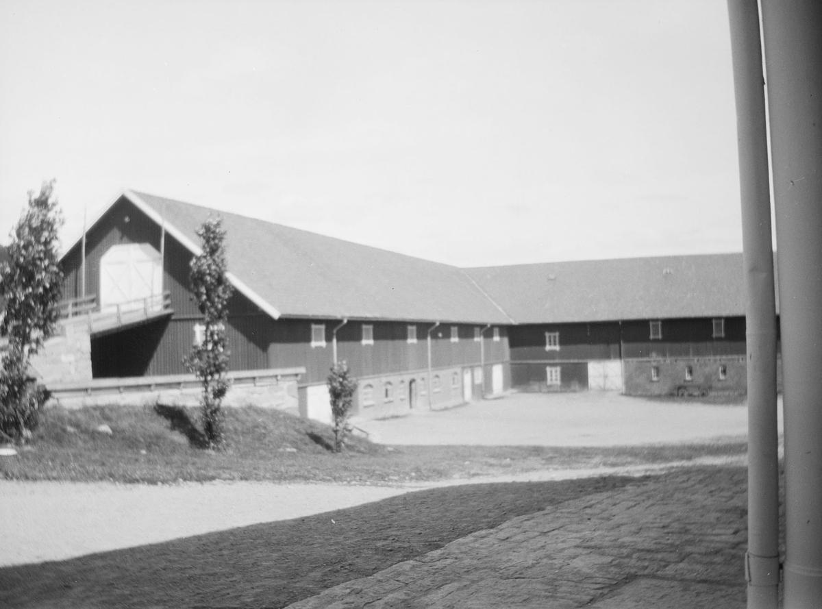 Sommerbilde fra gårdsplassen på Linderud Gård med stor låve, flere andre uthus og noen trær. I forgrunnen sees hjørnet av et hus med takrenne sam stein og grusbelagt gårdsplass.