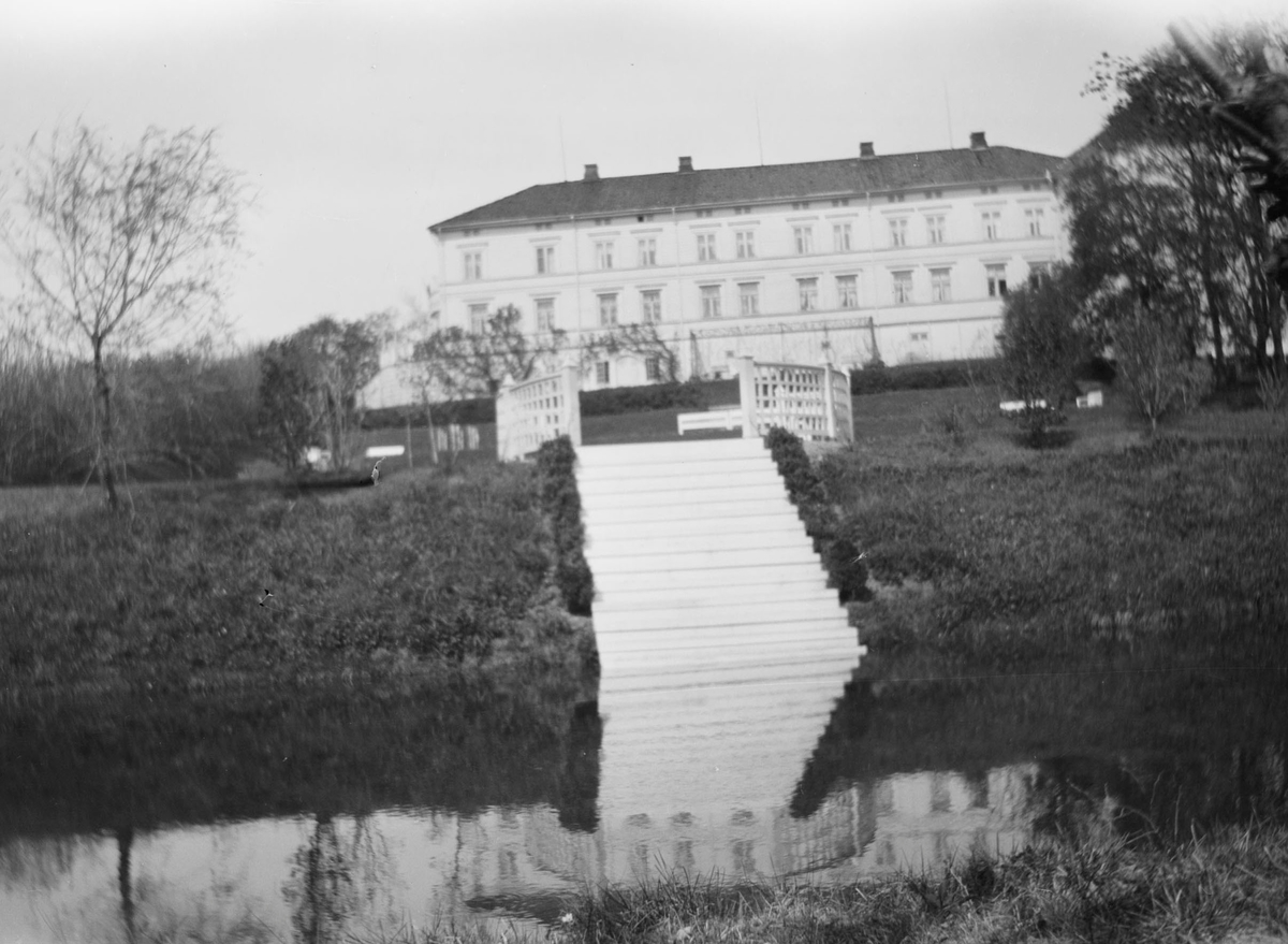 I forgrunnen sees dammen som er en del av hageanlegget på Linderud Gård. I bakgrunnen sees hekker, trær, trapper og avsatser med rekkverk samt hovedbygningen.