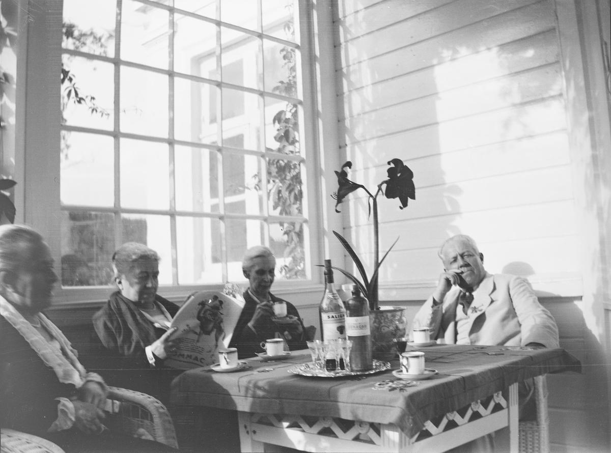 Christian Pierre Mathiesen med tre av søstrene: Julie til venstre, Louise i midten, Anna til høyre - sitter i kurvmøbler rundt et bord på verandaen på Linderud gård.