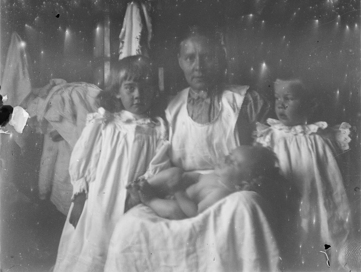 En kvinne i hvitt forkle sitter ned et nakent spedbarn i fanget. Hun har et barn på hver side.