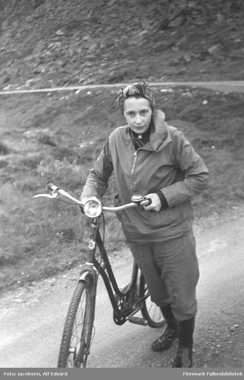 Aase Jacobsen på sykkeltur fra Rypefjord. Sykkelen er en ganske mørk DBS damesykkel med lykt montert på det blanke styret. En ringeklokke er montert på venstresiden av styret. Hun har mørke sko og mørke strømper. Hun er også iført en ganske lys bukse som går til knærne, en turjakke i omtrent samme farge som buksa. Jakken har også mørke krus rundt håndleddene, glidelås foran og en stor hette. På hodet har hun et mønstre tørkle. Veien har grusdekke og endel gress og stein ses i terrenget. Bak henne går en ganske bratt fjellside oppover. Fjellsiden er stort sett dekket av stein.
