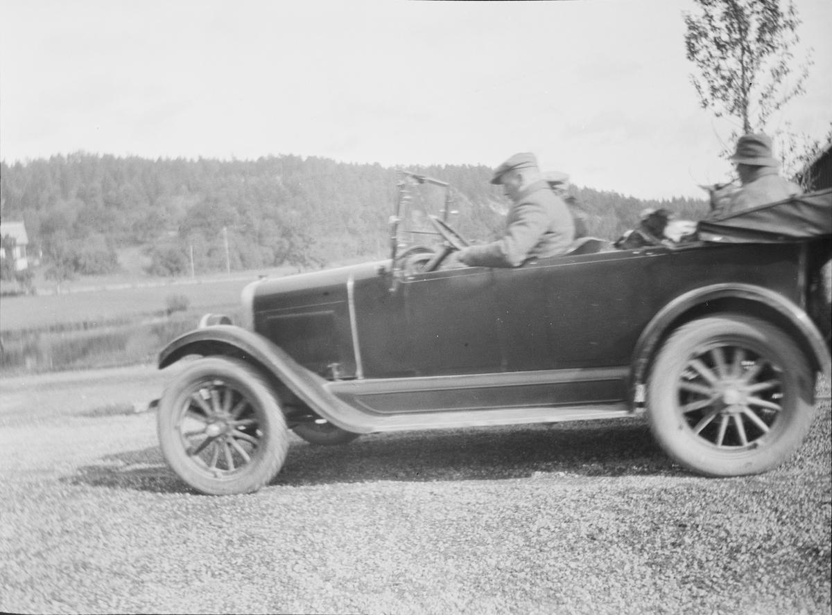 Bil fotografert på gårdsplassen til Linderud Gård. To personer sitter foran i bilen og en piperøkende person sitter i baksetet.