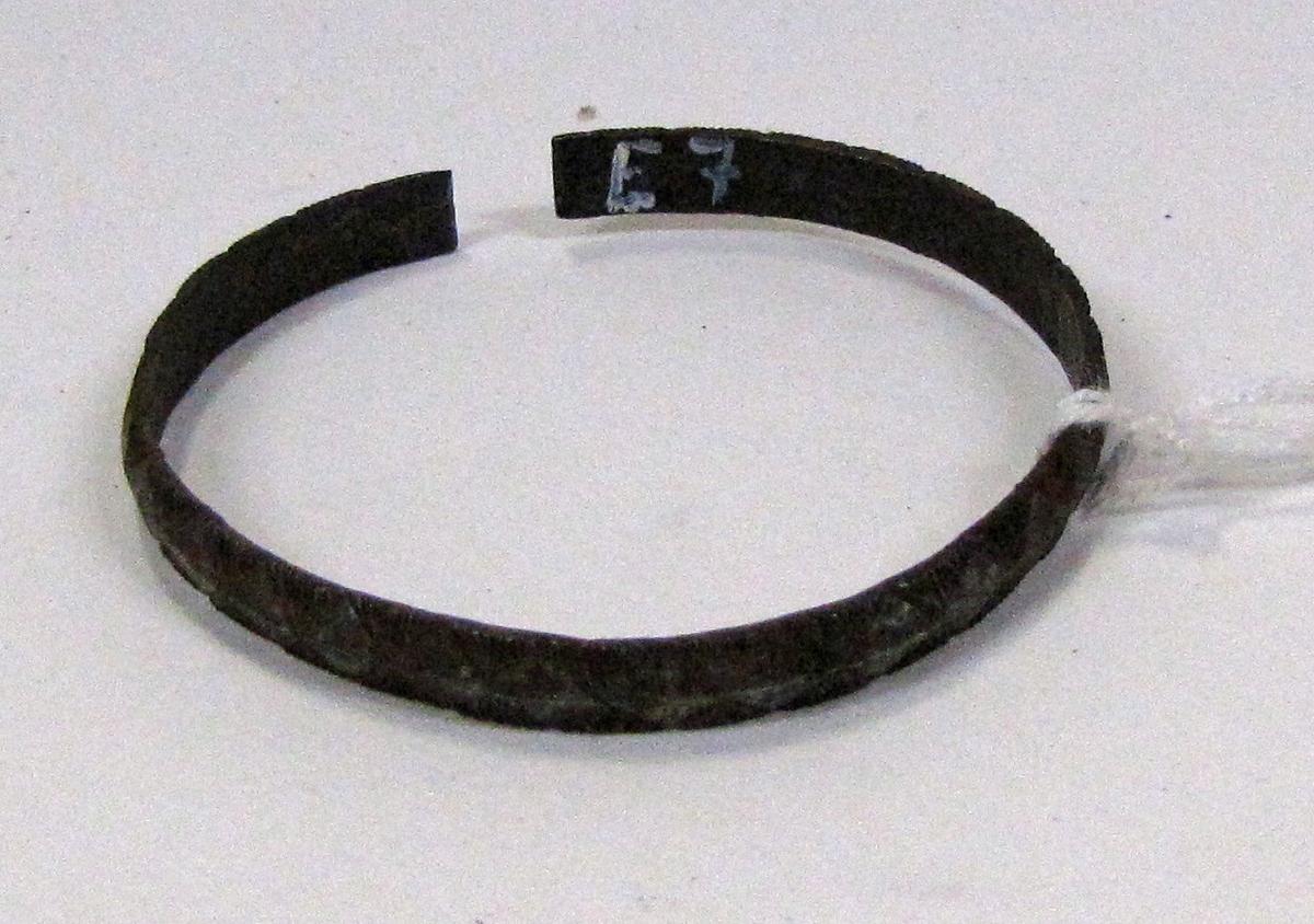 """Ett av nio smala öppna armband av järn med räfflor. Utan etikettnummer, dock vidhängande bricka med """"L"""" på. Enligt senare funnen förteckning L = Nio armringar av stål. ( Katalog 7 ) . Gåva av Eriksson ( den 7/3 68 ).  Ristat rombmönster, 5,5 cm bred. Jämför E 00 005: c.  Föremålet tillhör den etnografiska samlingen."""