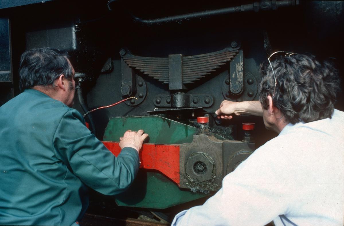 Lokomotivkontrollører i NSB, John Hjelde og Arvid Lie, instruerer personale på den nye museumsjernbanen. Her demonstreres smøring av akselkasse på diesellokomotiv nr. 10 (Ruston).