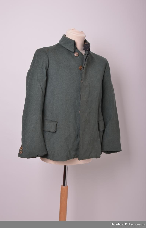 Mørk grønn jakke med svak A-fasong. Skjult knappestolpe og høy krave med korte snipper. Ikke originale knapper.
