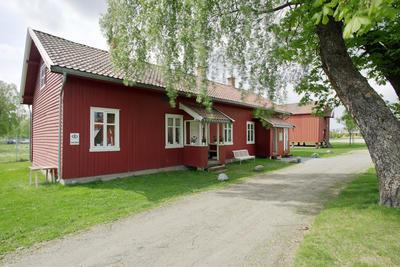 Rødt langt to etasjes hus med to innganger.