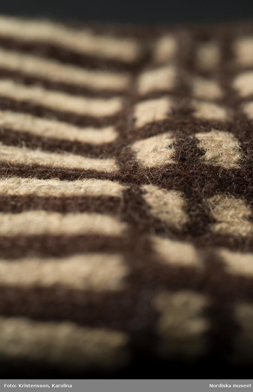 En udda tumvante stickad av mörkbrunt och gråvitt ullgarn i rumönster, mudden stickad  randig i samma färger  Mycket  lagad med både svart och gråvitt ullgarn  på handens och tummens insida.  /Berit Eldvik 2013-03-18