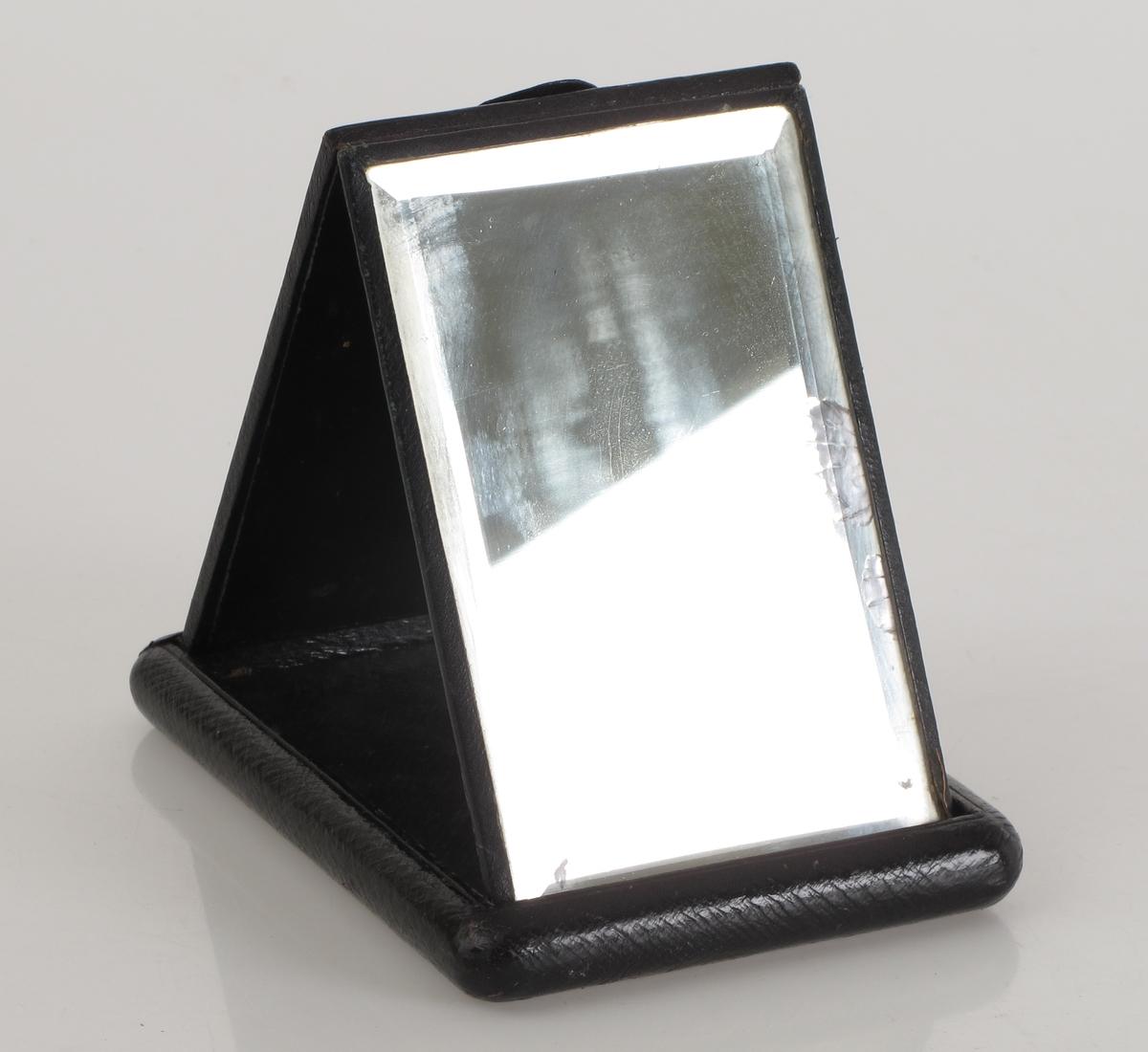 Lommebarberstell med skinntrukket etui trukket m. sort maroquin. Kan åpnes og et speil m. slepen kant oppstilles. Hempe i lokket.