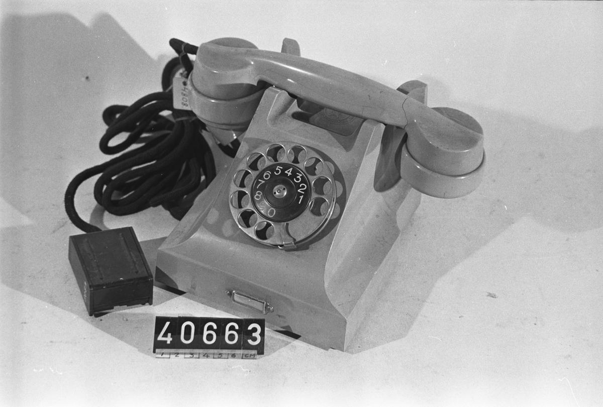 Telefonapparat BC 330, ändstationsapparat för AT-system. Bordapparat modell m33 av grå plast med fingerskiva av förnicklad mässing och textilklätt apparatsnöre anslutet till väggplint med lock av svartlackerad plåt. Märkt:4808.