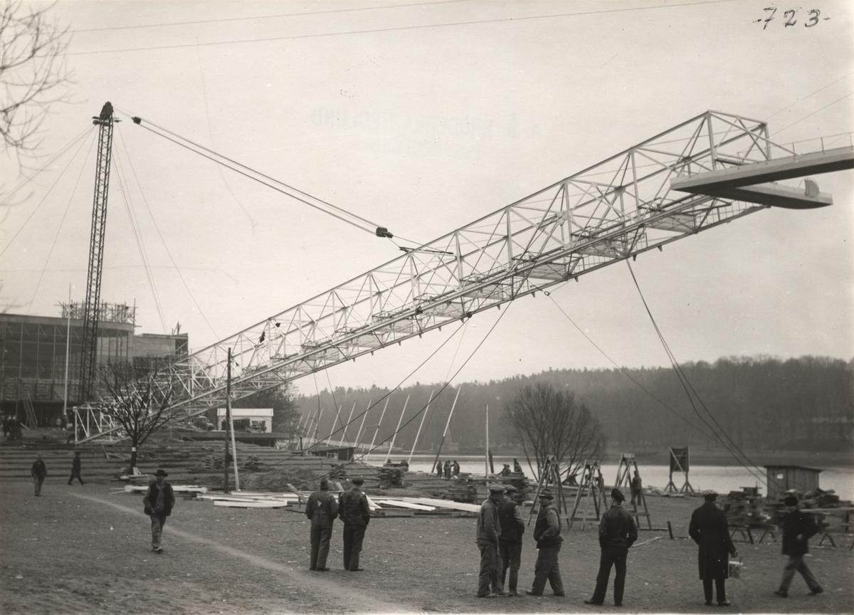 Aktiebolaget Bröderna Hedlund. Reklammasten för Stockholms-utställningen under resning den 19 jan 1930. Masten, vars tvärsektion var 3 x 3 m och c:a 80 m hög, vikt c:a 30 ton, restes på ungefär 3 timmar.